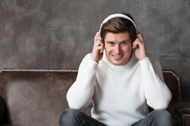 座っている間ヘッドフォンで音楽を聞いている男性