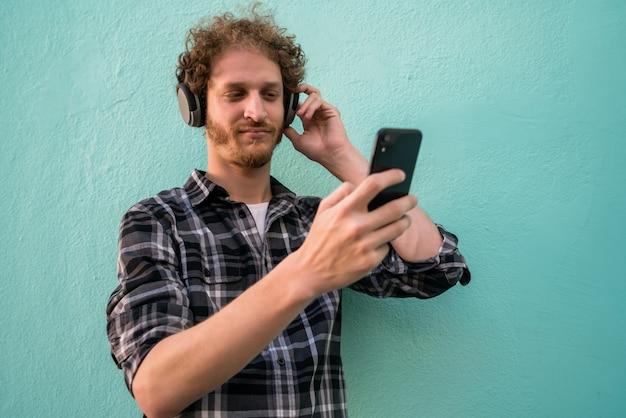 Человек слушает музыку с наушниками и мобильным телефоном