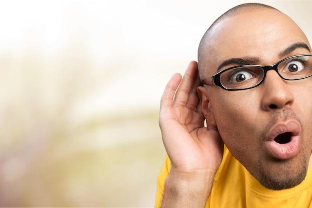 耳に手で聞いている人、コピースペースの背景