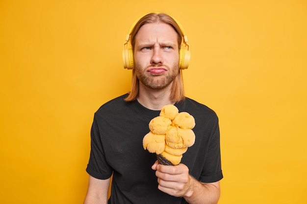 Man listens music via stereo headphones holds big cone appetizing ice cream feels displeased dressed in black t shirt isolated on yellow