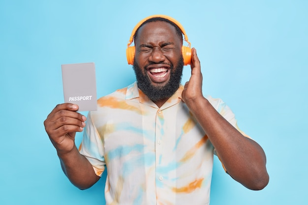 Man listens music via wireless headphones laughs put positively holds passport going to have travel