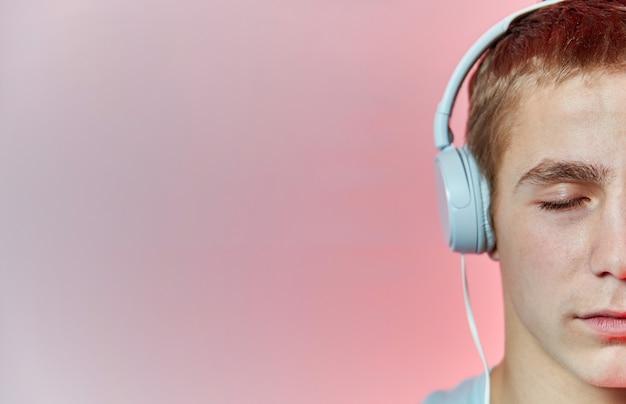 남자는 파란색과 빨간색 벽에 전화에서 헤드폰으로 음악을 듣는다.
