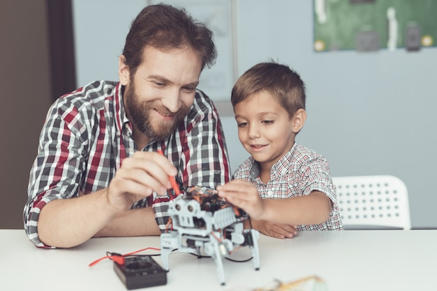 The man and the little boy measure the robot's performance.