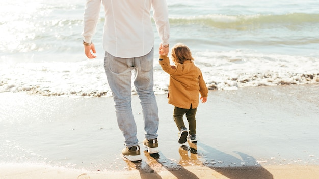 Man and little boy standing on seashore