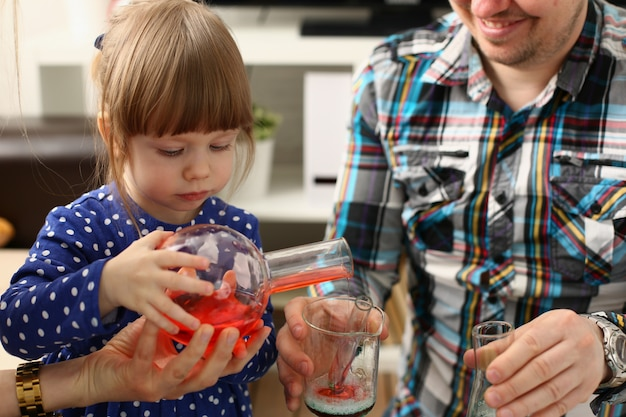 Man and little girl play with colourful liquids