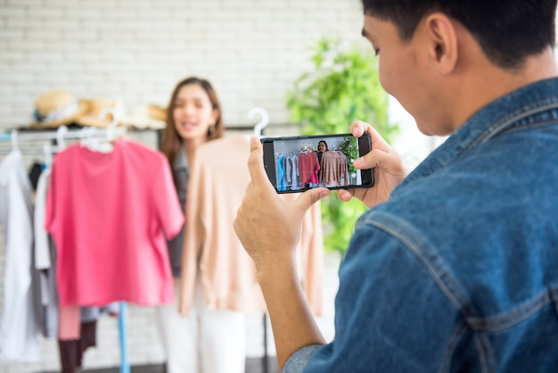 Man live video streaming by smartphone to selling clothes by fashion blogger