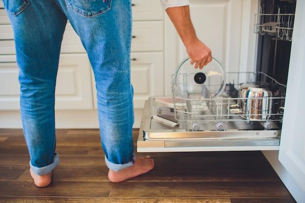 男は台所で食器洗い機をロード