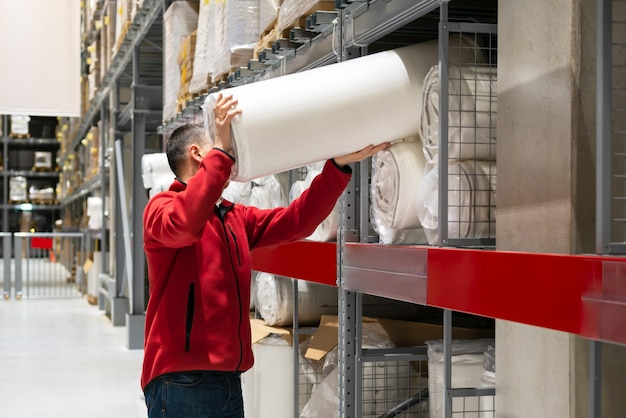 Man loading roll of mattress in warehouse