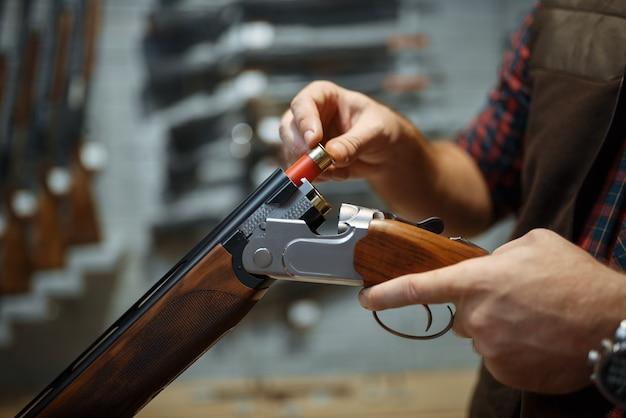 男はライフル、銃店のインテリアをロードします。武器店、狩猟、スポーツ射撃の趣味のスタンドにハンターのための機器