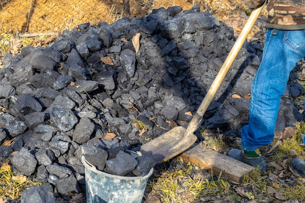 A man loads coal into a bucket with a shovel. heating a country house during the cool season in autumn and winter.