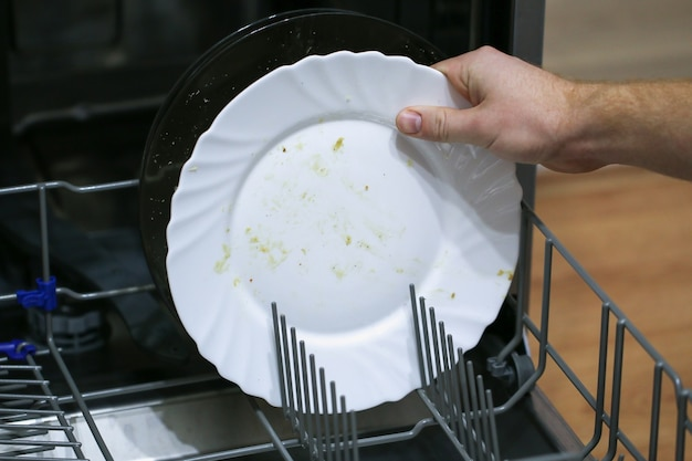 A man loads dirty dishes, plates, spoons, forks, cutlery into the dishwasher tray.