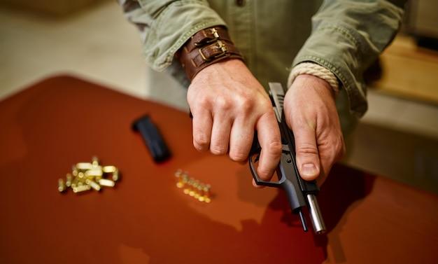 男は銃の店で銃弾を銃に装填します