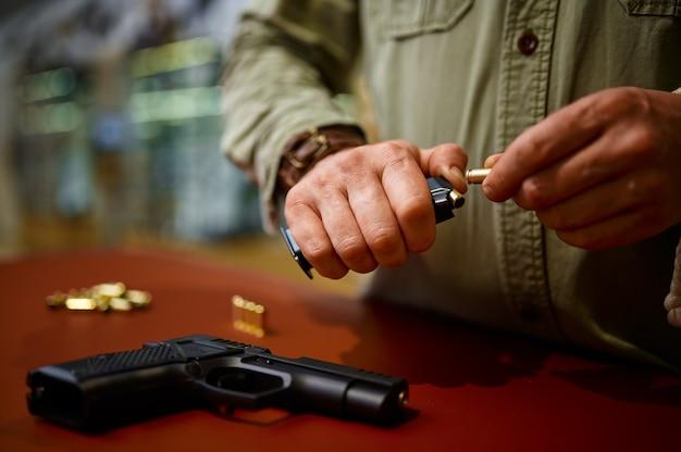 男は銃の店で弾丸で雑誌をロードします。武器屋のインテリア、弾薬と弾薬の品揃え、銃器の選択、射撃の趣味とライフスタイル、護身術