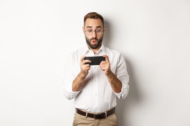 Человек смотрит изумленно на мобильный телефон, стоя на белом фоне.