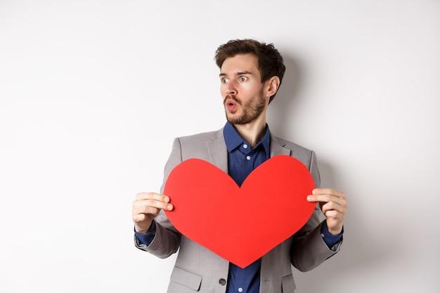 흰색 배경 위에 발렌타인 데이에 서있는 큰 붉은 심장 컷 아웃을 들고 아름다운 사람을 놀라게하는 남자. 공간 복사