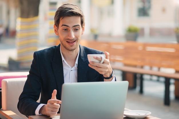Человек смотрит и показывает удивлен к ноутбуку