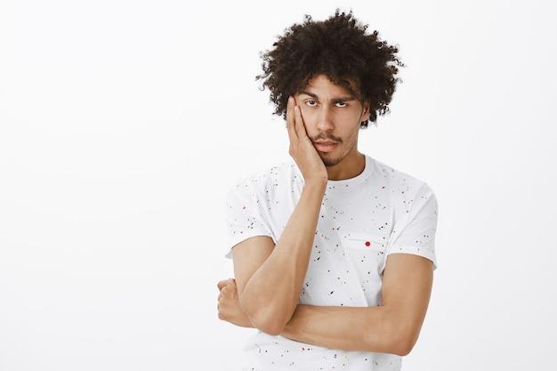 Uomo che sembra infastidito. l'uomo guarda riluttante e annoiato, sentendosi insoddisfatto o assonnato
