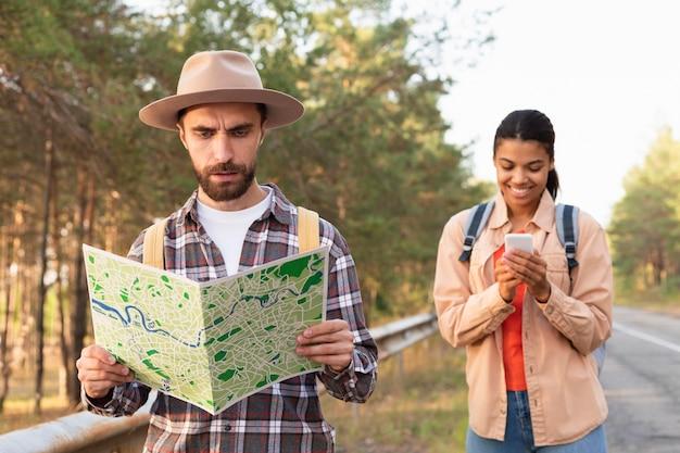彼のガールフレンドと一緒に旅行中に地図を見ている男