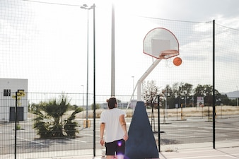 Man looking at basketball going through hoop