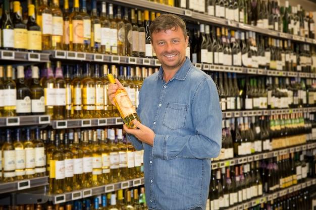 Человек смотрит на бутылку вина в супермаркете