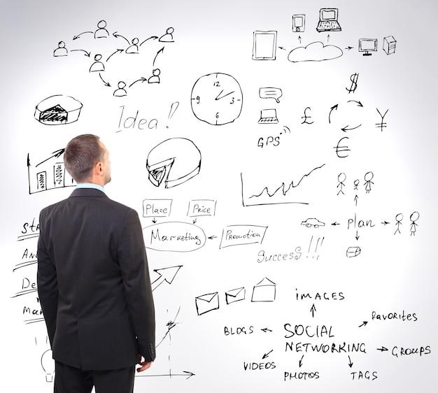 벽에 비즈니스 전략을 보고 있는 남자