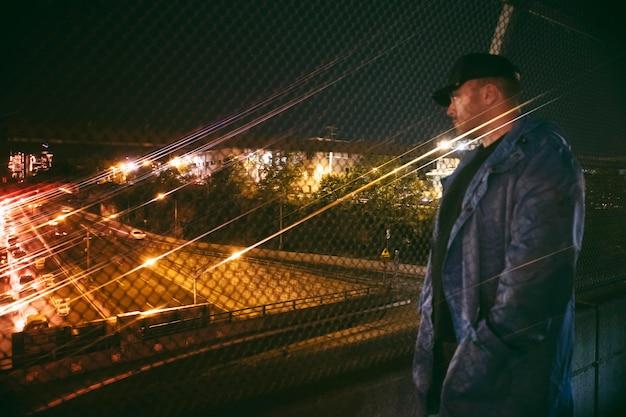 橋の上で夜に忙しい街の高速道路を見ている男