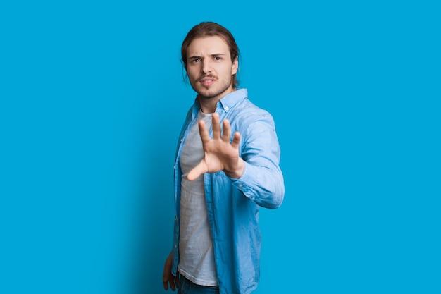 カメラを見て、青い壁でポーズをとっている間、何かを止めたいように身振りで示す男