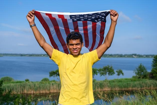 카메라를 보고 자랑스럽게 팔에 미국 국기를 들고 있는 남자