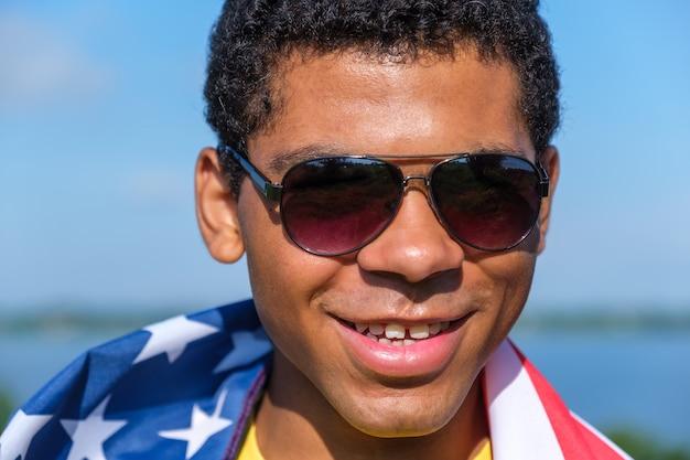 카메라를 보고 자랑스럽게 어깨에 미국 국기를 들고 있는 남자
