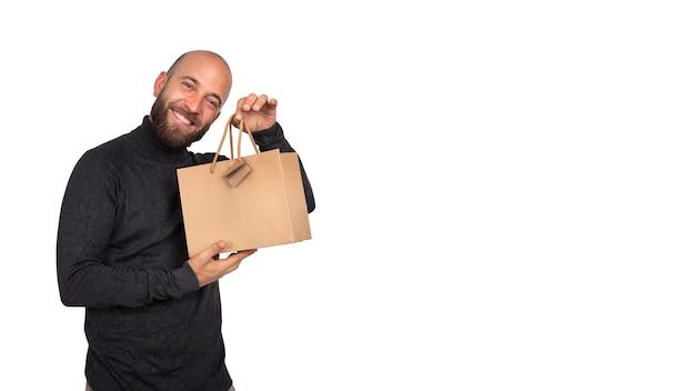 カメラを見ている男は白い背景のバナー画像に買い物袋を示していますコピースペースブラックフライデー