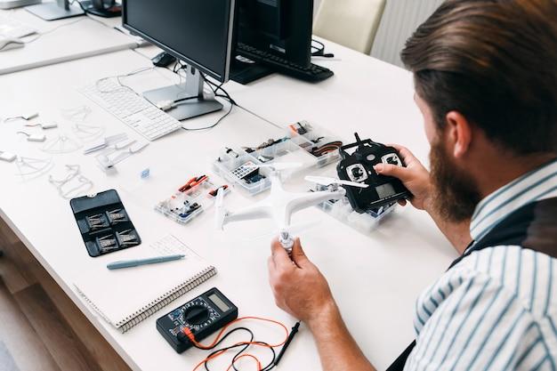 Человек смотрит на дрон и дистанционное управление. перед полетом инженер проверяет связь квадрокоптера с передатчиком. тестирование нового электронного устройства