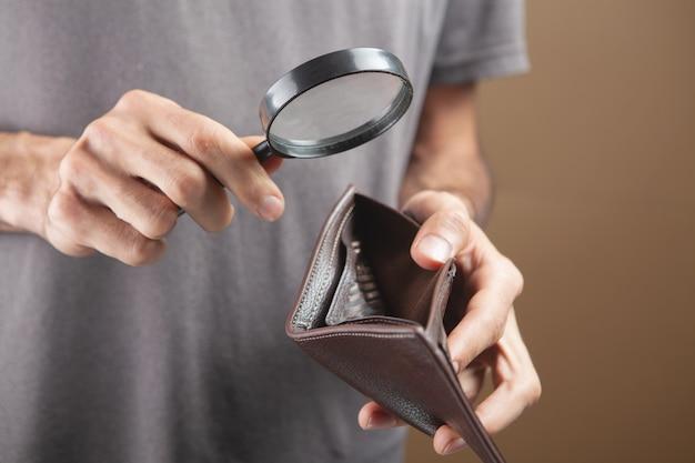 Человек смотрит на пустой бумажник с увеличительным стеклом на коричневом фоне