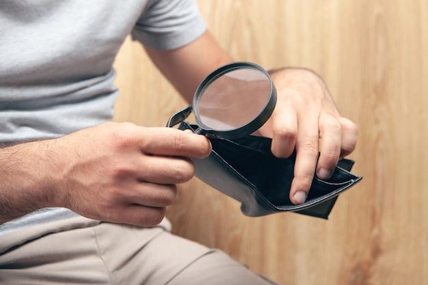 나무 배경에 돋보기가 있는 빈 지갑을 보고 있는 남자
