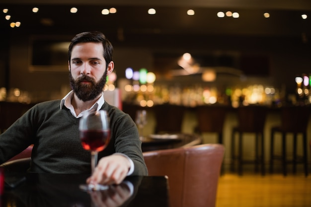 Человек смотрит на бокал красного вина