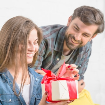Man looking at his girlfriend unwrapping valentine gift