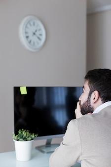 コンピュータでメモを見ている男