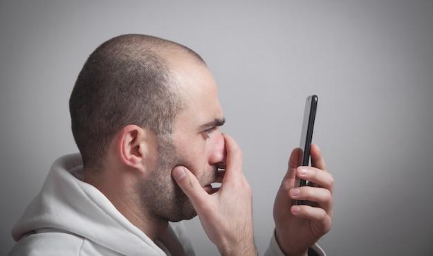 携帯電話の画面を見ている男。ソーシャルメディア中毒