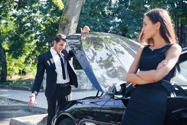 Человек смотрит на открытый капот в сломанной машине