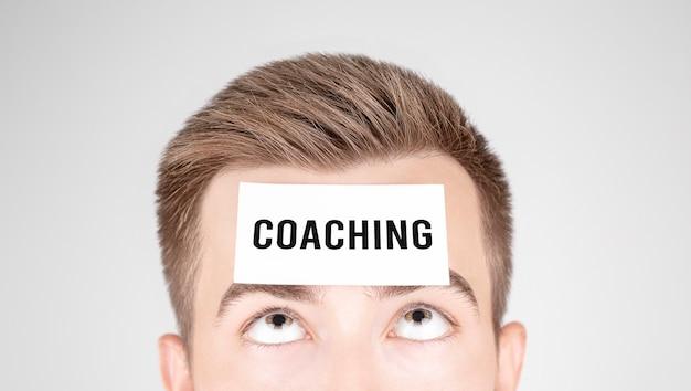 額にコーチングという言葉を貼り付けて紙を見ている男