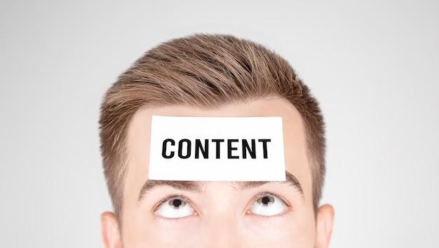 額にcontentという言葉が貼り付けられた紙を見ている男