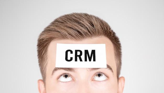 額にcrmという単語が貼り付けられた紙を見ている男