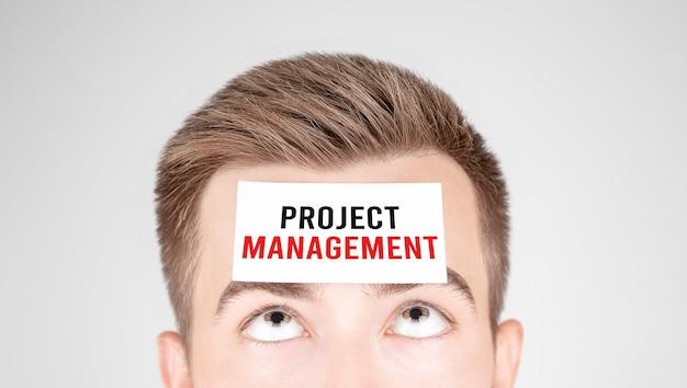 彼の額に貼り付けられたプロジェクト管理という言葉で紙を見ている男
