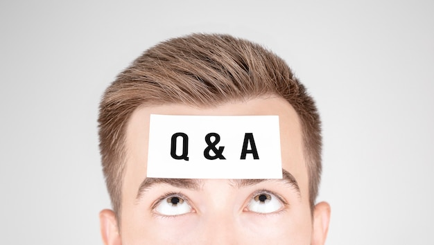 Мужчина смотрит на бумагу со словом q и a, наклеенным на его лоб