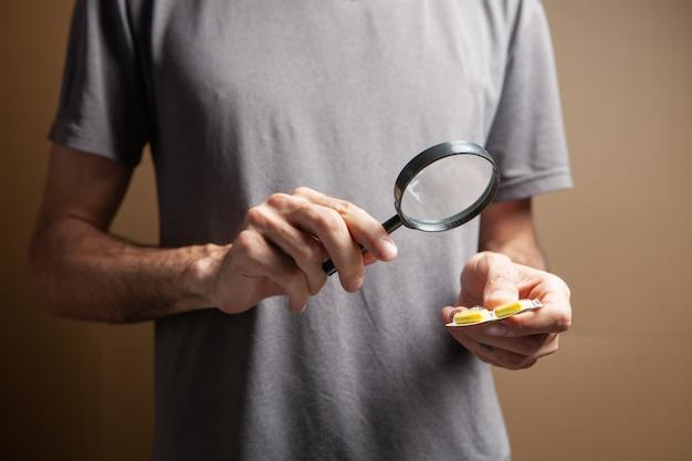 茶色の背景に拡大鏡で錠剤を見ている男