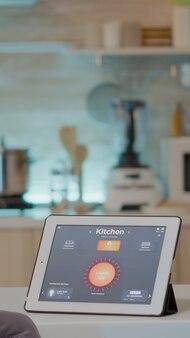 ハイテクアプリケーションで光を制御する台所のテーブルに配置されたインテリジェントなソフトウェアでタブレットを見ている男。