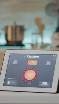 キッチンの机の上に置かれたワイヤレス照明自動化ソフトウェアを備えたタブレットを見ている男性、スマートシステムを備えた家、照明をオンにします。電気効率を制御するハイテクアプリを搭載したデジタルタブレット