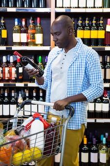 Мужчина смотрит на бутылку вина в продуктовом отделе