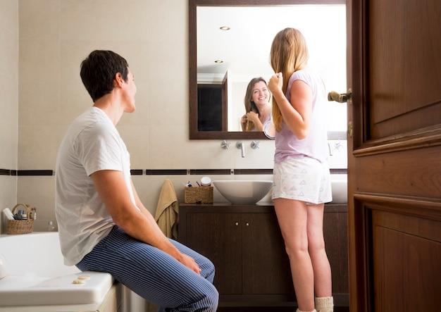 鏡の中を見る女性を見ている男