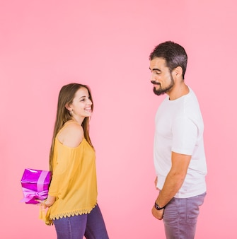Man looking at wrapped gift hiding from boyfriend
