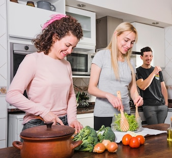 Man looking at young women preparing salad on table